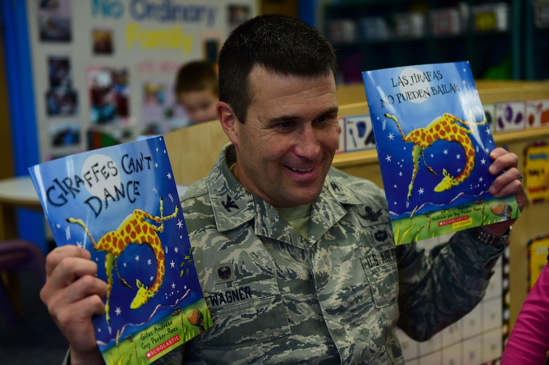 "Col. John Wagner, 460th Space Wing commander, displays a book April 13, 2016, at the Crested Butte Child Development Center on Buckley Air Force Base, Colo. One Book 4 Colorado, a program designed to promote early literacy skills, chose the book ""Giraffes Can't Dance"" for 2016 to distribute to 4-year-olds across Colorado. (U.S. Air Force photo by Airman 1st Class Gabrielle Spradling/Released)"
