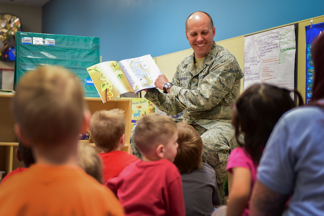 "Col. Scott Romberger, 460th Space Wing vice commander, reads ""Giraffes Can't Dance"" to children at the A-Basin Child Development Center April 14, 2016, on Buckley Air Force Base, Colo. The book is part of the One Book 4 Colorado program, a statewide annual initiative that offers free copies of the same book to every 4-year-old in Colorado in order to help create a culture of literacy. (U.S. Air Force photo by Staff Sgt. Katrina M. Brisbin/Released)"