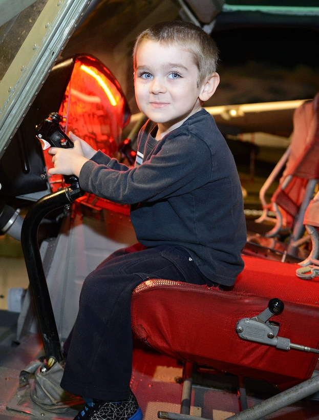 Silas Kain Ruest, 4, takes the pilot's seat of a helicopter displayed in Hangar One. (U.S. Air Force photo by Tommie Horton)