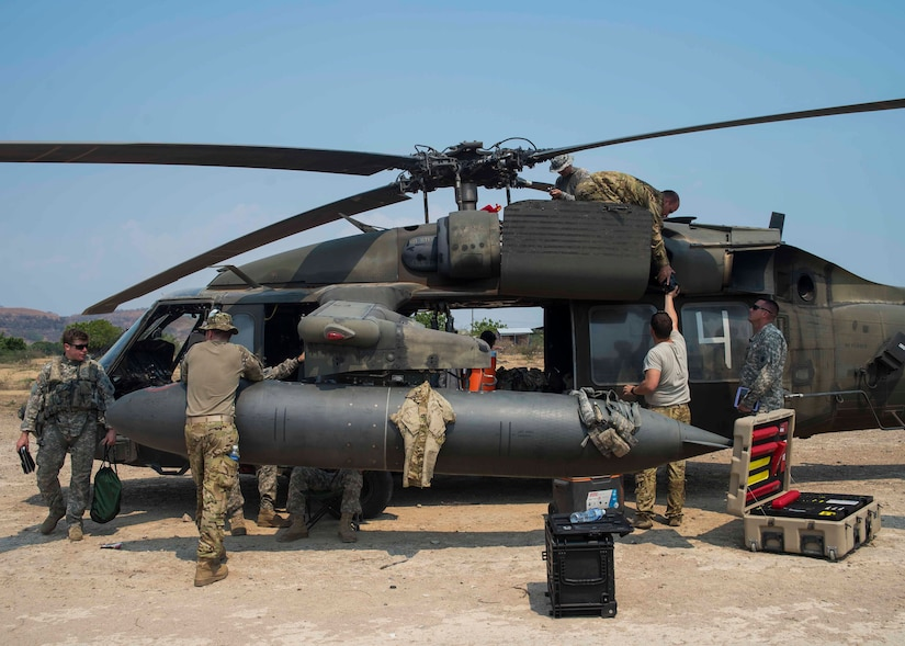 Members of the 1st Battalion, 228th Aviation Regiment, Joint Task Force Bravo at Soto Cano Air Base, Honduras, perform maintenance on a UH-60 Blackhawk helicopter at a forward area refueling point in Honduras, April 14, 2016. The FARP acted as a temporary rest and refuel point for aircraft and aircrew members, while conducting deck landing qualifications over the Caribbean Sea. (U.S. Air Force photo by Staff Sgt. Siuta B. Ika)