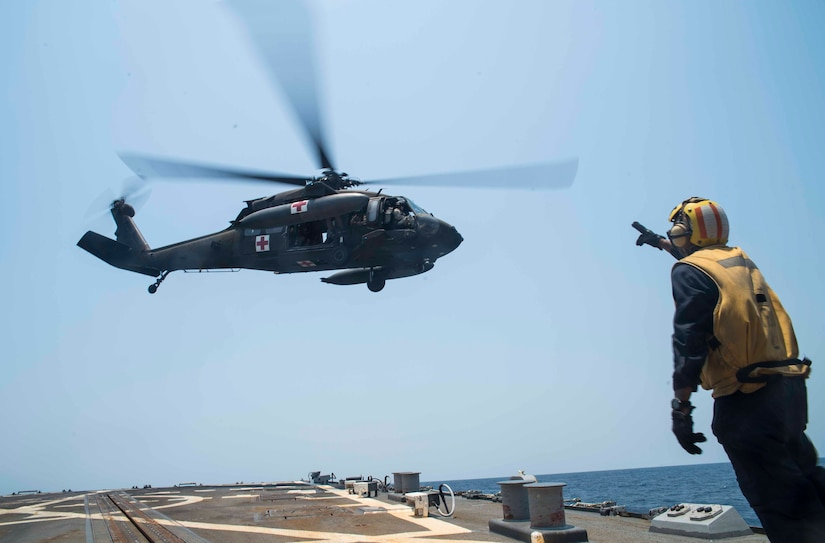 A U.S. Navy sailor signals to the crew of a UH-60 Blackhawk assigned to the 1st Battalion, 228th Aviation Regiment, Joint Task Force Bravo at Soto Cano Air Base, Honduras, during the Blackhawk crew's deck landing qualification off the coast of Honduras, April 14, 2016. Seventeen pilots and 16 crew chiefs qualified, performing approximately 80 deck landings on the USS Lassen. (U.S. Air Force photo by Staff Sgt. Siuta B. Ika)