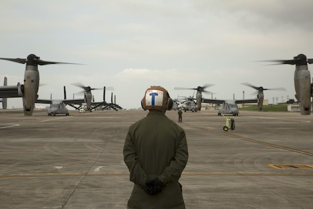 """A Marine waits to guide MV-22 Ospreys with Marine Medium Tiltrotor Squadron 265, 31st Marine Expeditionary Unit, during their takeoff April 17 on Marine Corps Air Station Futenma. United States Forces, Japan is providing operational airlift support in coordination with the Government of Japan's efforts to provide relief following the devastating earthquake near Kumamoto. """"We express our deepest condolences to all of those affected by the recent earthquakes in Kyushu,"""" said Lt. Gen. John Dolan, commander of USFJ. """"To the people of Japan and the region affected by this tragedy we send our heartfelt sympathies. The men and women of U.S. Forces, Japan stand with you during this difficult time."""" The long-standing alliance between Japan and the U.S. allows U.S. military forces in Japan to provide rapid, integrated support to the Japanese Self-Defense Forces and civil relief efforts."""