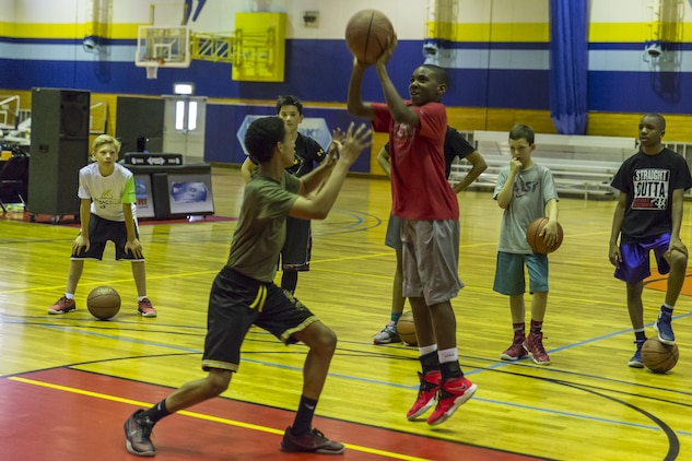 Chandler Pigge, a seventh-grader at Matthew C. Perry High School, shoots the basketball as Amin Mice, a ninth-grader at M.C. Perry High School, attempts to block during the 2016 Mainland Basketball Association Spring Basketball Camp at Marine Corps Air Station Iwakuni, Japan, April 13, 2016. Student athletes between the ages of 12 and 18 attended the camp seeking to improve their knowledge of skills and basketball such as shooting, passing, dribbling, rebounding and defending. Point Guard College attended the camp to teach competitors to play smart basketball and become good leaders during practice, games and everyday life. (U.S. Marine Corps photo by Lance Cpl. Aaron Henson/Released)