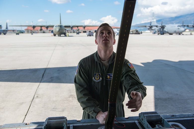 Senior Airman Alec Miller, a loadmaster from the 96th Airlift  Squadron, secures the end of a parachute to the ramp of a C-130 at Aviano AB, Italy, on April 10. (U.S. Air Force photo by Staff Sgt. Trevor Saylor)