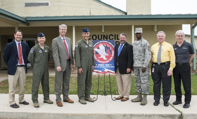 From left to right: Brian James, Schertz executive director of development, Lt. Col. Emil Bliss, 12th Flying Training Wing community initiatives director, John Kessel, Schertz city manager, Col. Matthew Isler, 12th FTW commander, Michael Carpenter, mayor of Schertz, Chief Master Sgt. Troy Palmer, 12th FTW command chief, Dudley Wait, executive director of operations, and Robin Thompson, Schertz place 5 council member, unveil the new city sign in front of the Schertz Council Chambers April 12, 2016. Joint Base San Antonio-Randolph and the city of Schertz are committed to keeping residents informed about aircraft training in the local area and the effects it may have on noise levels.