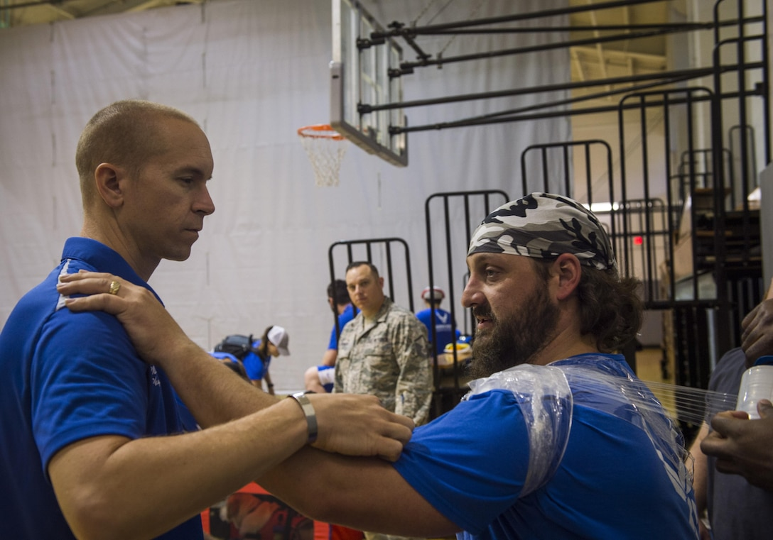 Maj. (Dr.) Sean Martin, the chief of sports medicine with Air Force Special Operations Command Office of the Surgeon General, helps retired Tech. Sgt. Cory Anderson, a wounded-warrior athlete, ice his shoulder after sitting volleyball practice at Hurlburt Field, Fla., April 4, 2016. Teams participate in seven sports to include archery, cycling, shooting, sitting-volleyball, swimming, track and field, and wheelchair basketball. (U.S. Air Force photo by Staff Sgt. Marleah Miller)
