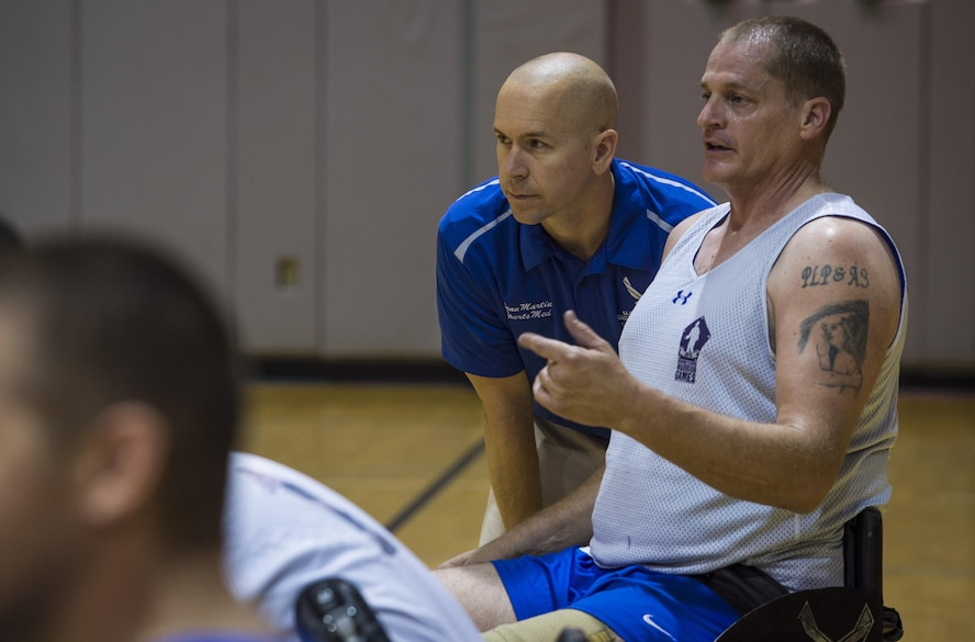 Maj. (Dr.) Sean Martin, the chief of sports medicine with Air Force Special Operations Command Office of the Surgeon General, talks to retired Tech. Sgt. Pat Young, a wounded-warrior athlete, during wheelchair basketball practice at Hurlburt Field, Fla., April 5, 2016. Martin and other medical technicians provide extra services to the athletes during the training camp to ensure as much of their time as possible is spent in the competition and not on the sideline. (U.S. Air Force photo by Staff Sgt. Marleah Miller)