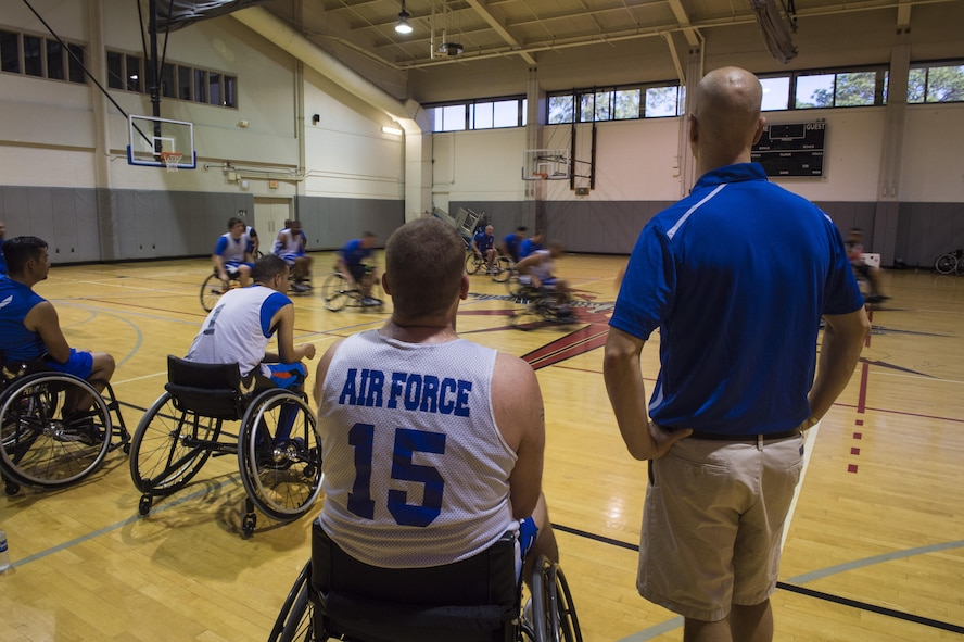 Maj. (Dr.) Sean Martin, right, the chief of sports medicine with Air Force Special Operations Command Office of the Surgeon General, talks to retired Tech. Sgt. Pat Young, left, a wounded-warrior athlete, during wheelchair basketball practice at Hurlburt Field, Fla., April 5, 2016. The Wounded Warrior Games, an annual event established in 2010, offers a competition for wounded, ill and injured service members, and veterans. (U.S. Air Force photo by Staff Sgt. Marleah Miller)