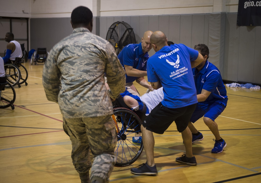 Maj. (Dr.) Sean Martin, center, the chief of sports medicine with Air Force Special Operations Command Office of the Surgeon General, and volunteers help a wounded-warrior athlete during wheelchair basketball practice at Hurlburt Field, Fla., April 5, 2016. The Wounded Warrior Games, an annual event established in 2010, offers a competition for wounded, ill and injured service members and veterans. (U.S. Air Force photo by Staff Sgt. Marleah Miller)