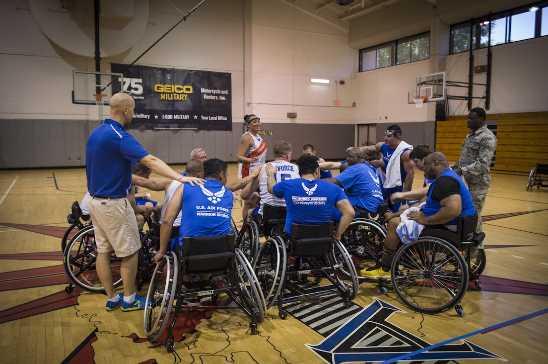 Maj. (Dr.) Sean Martin the chief of sports medicine with Air Force Special Operations Command Office of the Surgeon General, joins in the huddle with wounded-warrior athletes after wheelchair basketball practice at Hurlburt Field, Fla., April 5, 2016. The Warrior Games consist of seven sports including archery, cycling, shooting, sitting-volleyball, swimming, track and field, and wheelchair basketball. (U.S. Air Force photo by Staff Sgt. Marleah Miller)