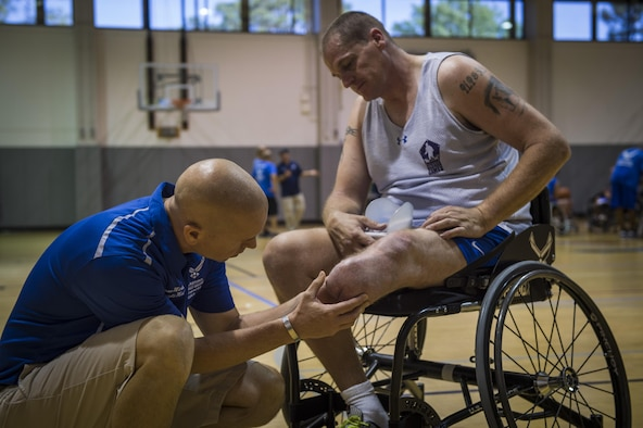 Maj. (Dr.) Sean Martin the chief of sports medicine with Air Force Special Operations Command Office of the Surgeon General, checks on retired Tech. Sgt. Pat Young's, a wounded-warrior athlete, leg after wheelchair basketball practice at Hurlburt Field, Fla., April 5, 2016. Martin and other medical technicians provide extra services to the athletes during the training camp to ensure as much of their time as possible is spent in the competition and not on the sideline. (U.S. Air Force photo by Staff Sgt. Marleah Miller)