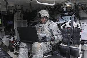 A soldier assigned to the 780th Military Intelligence Brigade prepares his equipment inside a Stryker vehicle during an integrated cyber exercise at Joint Base Lewis-McChord, Wash., Oct. 21, 2015. Army photo