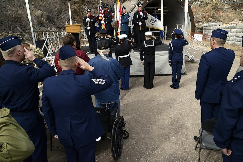 Attendees of the 50th anniversary rededication ceremony pay respect during the U.S. and Canadian national anthems at Cheyenne Mountain Air Force Station, Colo., April 15, 2016. After nearly five years of construction, Cheyenne Mountain AFS was declared fully operational April 20, 1966. Cheyenne Mountain AFS is owned by the 21st Space Wing at Peterson Air Force Base, Colo., and operated by the 721st Mission Support Group. (U.S. Air Force photo/Rob Bussard)