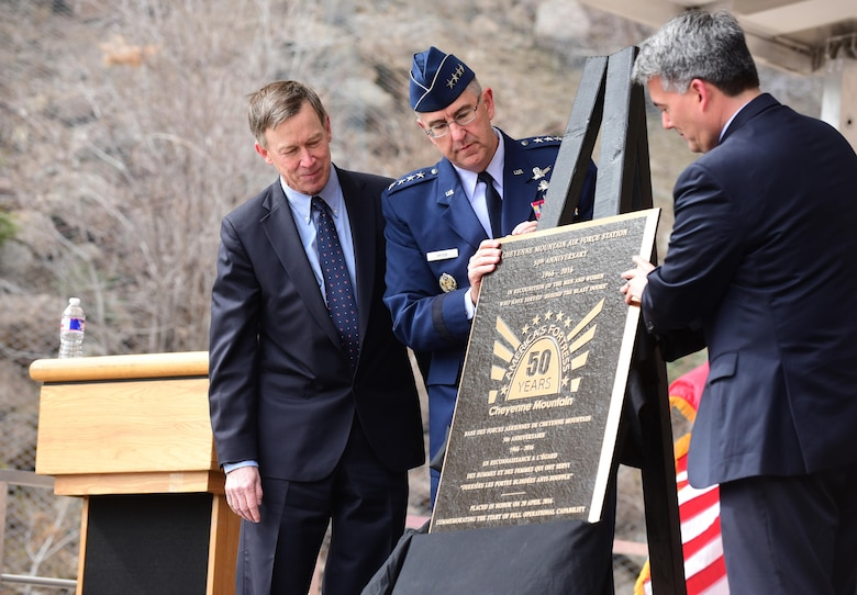 """Colorado Gov. John Hickenlooper, Gen. John Hyten, the Air Force Space Command commander, and Colorado Sen. Cory Gardner unveil the 50th anniversary rededication ceremony plaque at Cheyenne Mountain Air Force Station, Colo., April 15, 2016. With the nickname """"America's Fortress,"""" Cheyenne Mountain AFS is situated beneath 2,000 feet of granite and consists of 15 buildings resting on more than 1,300 enormous steel springs. Cheyenne Mountain AFS is owned by the 21st Space Wing at Peterson Air Force Base, Colo., and operated by the 721st Mission Support Group. (U.S. Air Force photo/Staff Sgt. Amber Grimm)"""