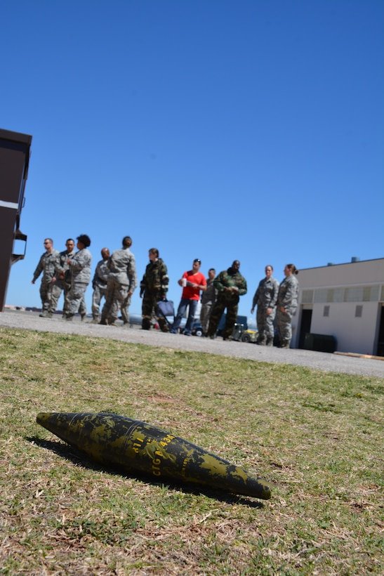 An unidentified explosive ordnance lies on the ground in a training area in the Reserve campus of Tinker Air Force Base, April 3, 2016.  Citizen Airmen in the background are working to identify the UXO as part of an Emergency Management Rodeo during the Super Unit Training Assembly held here April 2-5. The extended training allowed Reservists to complete all annual training and give them a opportunity to take one UTA off.  (U.S. Air Force photo/Maj. Jon Quinlan)