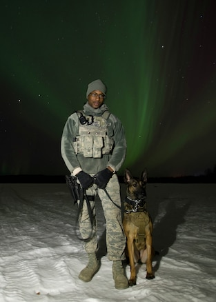 """U.S. Staff Sgt. Mathis Williams, a 354th Security Forces military working dog (MWD) handler, takes a break from a patrol with MWD Oopal in the dark at 30 degrees below zero March 7, 2016, at Eielson Air Force Base, Alaska, while the aurora borealis dances behind them. Military working dogs from Eielson work alongside the human defenders who stand """"Ready to go at 50 below"""" 24 hours a day protecting assets at the top of the world in the U.S. Air Force's Pacific theater of operations. (U.S. Air Force photo by Staff Sgt. Shawn Nickel/Released)"""