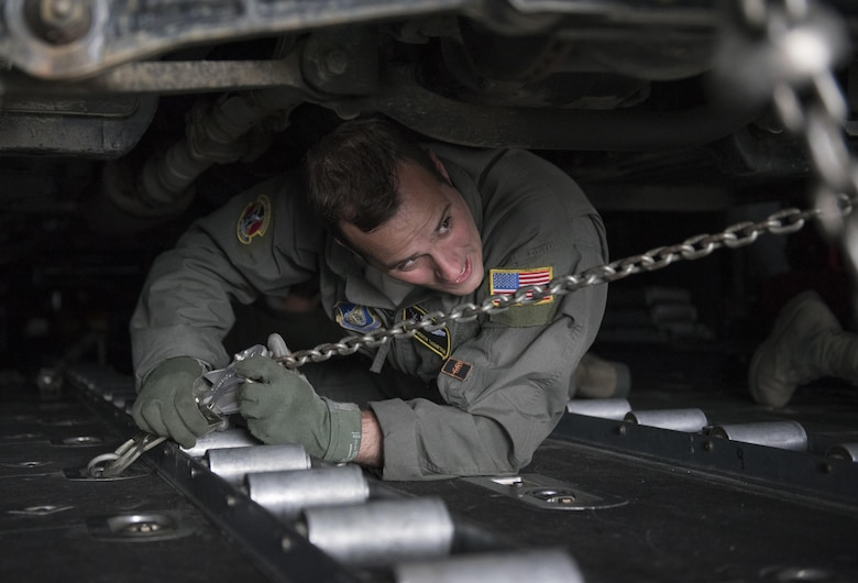 U.S. Air Force Staff Sgt. Andrew Thompson, 36th Airlift Squadron loadmaster, uses a chain to strap down a Japan Ground Self-Defense Force vehicle to a C-130 Hercules at Chitose, Hokkaido, Japan, April 18, 2016. The 374th Airlift Wing assisted the Government of Japan by airlifting vehicles and personnel from Hokkaido to the island of Kyushu in response of the recent earthquakes. (U.S. Air Force photo by Staff Sgt. Michael Washburn/Released)