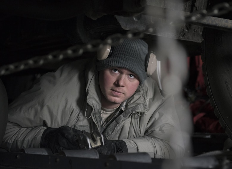 U.S. Air Force Senior Airman Brandon Ihnat, 374th Logistics Readiness Squadron air transportation specialist, checks two chains that secure a Japan Ground Self-Defense Force vehicle to a C-130 Hercules at Chitose, Hokkaido, Japan, April 18, 2016. The vehicles were being transported from Hokkaido to the island of Kyushu to assist in disaster relief efforts. (U.S. Air Force photo by Staff Sgt. Michael Washburn/Released)
