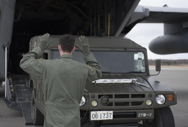 U.S. Air Force Senior Airman Dustin Brown, 36th Airlift Squadron loadmaster, marshals a Japan Ground Self-Defense Force vehicle into a C-130 Hercules at Chitose, Hokkaido, Japan, April 18, 2016. Two C-130s from Yokota Air Base, Japan picked up four vehicles and eight JGSDF members, airlifting them to Kumamoto Prefecture to assist in disaster relief following a series of earthquakes that struck Japan. (U.S. Air Force photo by Staff Sgt. Michael Washburn/Released)