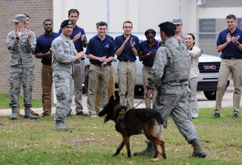 Air Force ROTC cadets applaud after a military working dog demonstration by Senior Airman Matthew Ratchford, 81st Security Forces Squadron military working dog handler and his dog Toki, during Pathways to Blue April 15, 2016, Keesler Air Force Base, Miss. Pathways to Blue, a diversity outreach event hosted by 2nd Air Force, the 81st Training Wing and the 403rd Wing, included more than 180 cadets from Air Force ROTC detachments from various colleges and universities. Cadets received hands-on briefings on technical and flying operations and an orientation flight in support of the Air Force's Diversity Strategic Roadmap program.  (U.S. Air Force photo by Kemberly Groue)