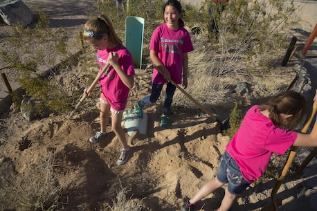 Girls Scouts of Troop 1744 cover up pipe used for new borrows for ambassador tortoises Thelma and Louise at the Combat Center's Archeology and Paleontology Curation Center April 12, 2016. The troop visited the installation to earn their Wildlife Habitat Badges which are earned through education on native wild animals and how they live. (Official Marine Corps photo by Cpl. Thomas Mudd/Released)