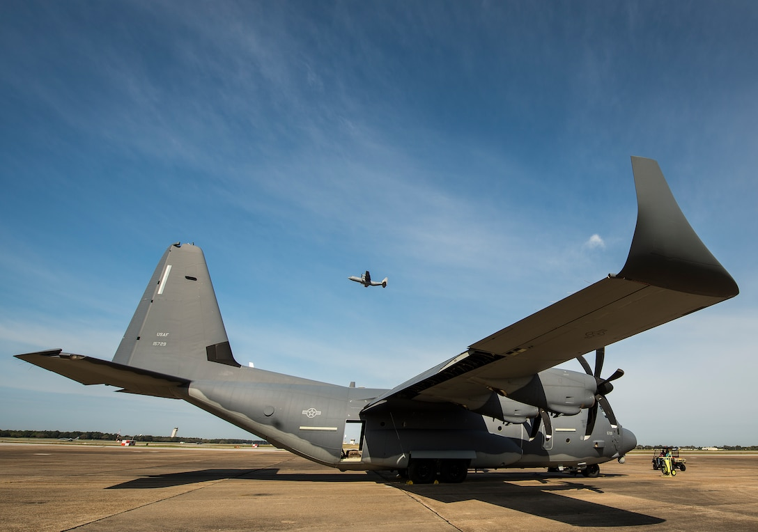 A modified MC-130J waits for its next mission as another C-130 lifts off above it at Eglin Air Force Base, Fla. The test aircraft has been fitted with vertical fins on each wing, called winglets.  The 413th Flight Test Squadron aircrew and engineers tested the modified aircraft over eight flights.  The goal of the tests was to collect data on possible fuel efficiency improvements and performance with the winglets and lift distribution control system installed.  (U.S. Air Force photo/Samuel King Jr.)