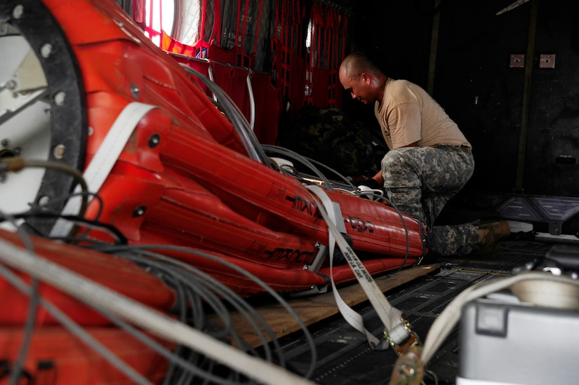 """U.S. Army Staff Sgt. King David, 1st Battalion, 228th Aviation Regiment CH-47 Chinook Crew Chief, secures a """"Bambi Bucket"""" in a CH-47 helicopter in preparation for Joint Task Force-Bravo personnel to assist with firefighting efforts in Panama April 15, 2016 at Soto Cano Air Base, Honduras. The Bambi Bucket holds up to 2000 gallons of water and allows fire suppression in areas inaccessible by land. (U.S. Army Photo by Martin Chahin/Released)"""