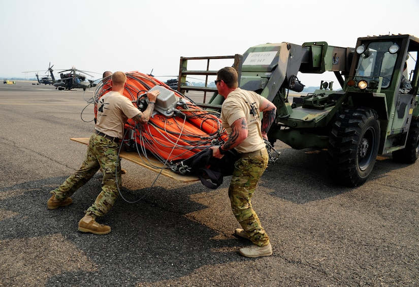 """U.S. Army Sgt. Derrick Auten, 1st Battalion, 228th Aviation Regiment flight platoon sergeant, and Sgt. 1st Class Christopher Gagnon, 1-228 AVN REGT Flight Engineer, prepare to load a """"Bambi Bucket"""" into a CH-47 Chinook helicopter in preparation for Joint Task Force-Bravo personnel to assist with firefighting efforts in Panama April 15, 2016 at Soto Cano Air Base, Honduras. (U.S. Army Photo by Martin Chahin/Released)"""
