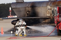 Firefighters practice extinguishing a fire around a staged downed aircraft during a Mass Casualty Exercise on Marine Corps Air Station Cherry Point, N.C., April 7, 2016.  The exercise was designed to simulate the response if an emergency were to occur. Annually, the air station is required to have exercises to ensure protocol and safety standards are met for potential emergencies. On years the biannual air show occurs, the training revolves around scenarios specific to that kind of event. (U.S. Marine Corps photo by Cpl. Jason Jimenez/Released)