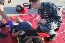 A Navy corpsman tends to a simulated casualty during a Mass Casualty Exercise on Marine Corps Air Station Cherry Point, N.C., April 7, 2016.  The exercise was designed to simulate the response if an emergency were to occur. Annually, the air station is required to have exercises to ensure protocol and safety standards are met for potential emergencies. On years the biannual air show occurs, the training revolves around scenarios specific to that kind of event. (U.S. Marine Corps photo by Cpl. Jason Jimenez/Released)