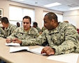 Staff Sgt. Marisol McKinley, left, Paralegal, and Sgt. Ronnie Payne, right, Human Resources Sergeant work together on applying the competencies of Master Resiliency Training. MRT is taught yearly to help soldiers better handle stress. 