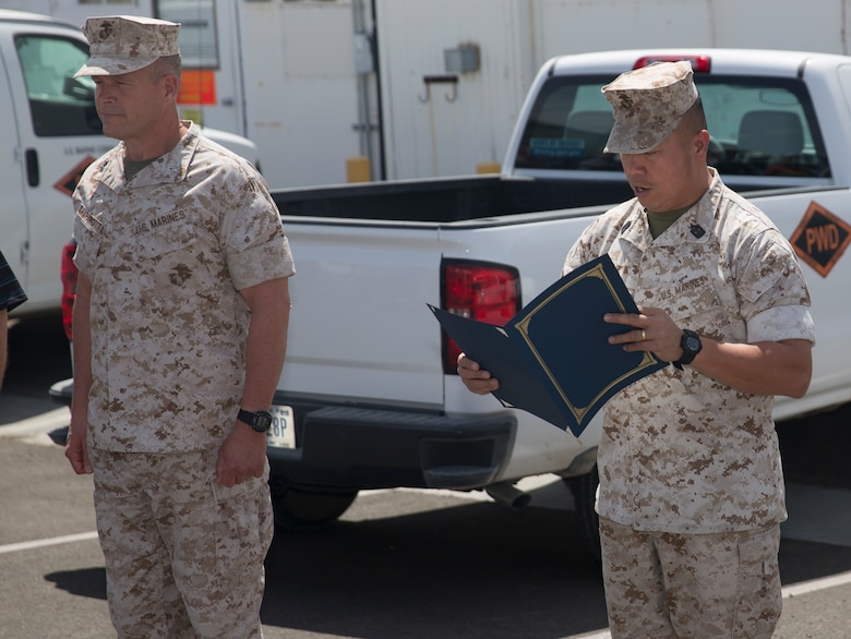 Sgt. Maj. Karl Villalino, Combat Center Sergeant Major, reads the Federal Length of Service award citation for Ricky Brennan, contract surveillance representative, Public Works Division, at the Combat Center's PWD, April 6, 2016. (Official Marine Corps photo by Cpl. Connor Hancock/Released)