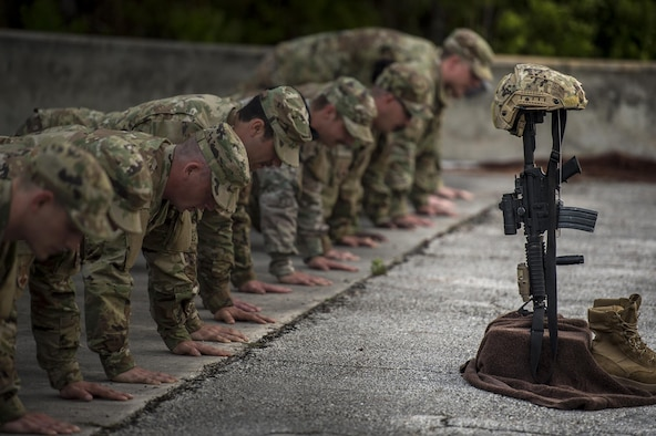 U.S. Air Force Airmen from the 93d Air Ground Operations Wing perform pushups as a tribute to fallen Terminal Air Control Party Airmen, April 15, 2016, at Avon Park Air Force Range, Fla. The Airmen gathered to pay tribute to Lt. Col William Schroeder, who served alongside many members of the 93d AGOW. (U.S. Air Force Photo by Senior Airman Ryan Callaghan/Released)