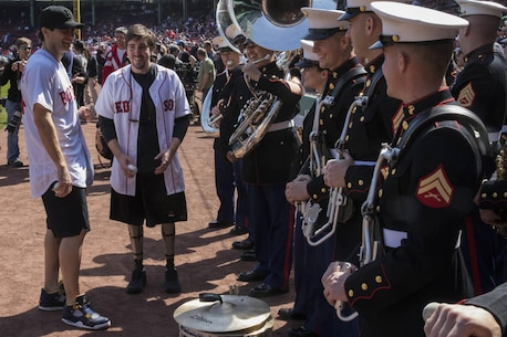 "Jake Gyllenhaal (left) and 2013 Boston marathon bombing survivor Jeff Bauman speak with Marines of the 2nd Marine Air Wing band prior to their performing the National Anthem at Fenway Park, April 18. The band opened for the Boston Red Sox baseball game and Gyllenhaal was at this year's marathon filming scenes for the upcoming movie ""Stronger,"" a biopic about Bauman during the marathon bombing."