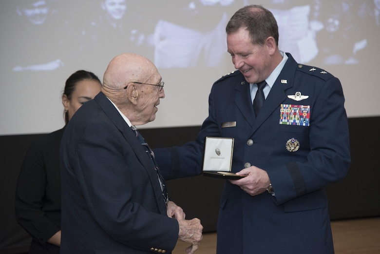 Lt. Col. Dick Cole presents a replica of his Congressional Gold Medal to Maj. Gen. James Hecker, 19th Air Force commander, April 18 at Joint Base San Antonio-Randolph. The Congressional Gold Medal is awarded to persons who have performed an achievement that has an impact on American history and culture that is likely to be recognized as a major achievement in the recipient's field long after the achievement.