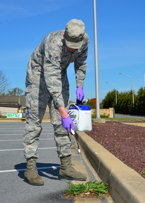 Airman 1st Class Jeremy Johnson, 436th Civil Engineer Squadron pest control journeyman, sprays weed killer around the Commissary parking lot during a spring cleanup event April 18, 2016, at Dover Air Force Base, Del. The 436th CES organized the event and had assistance from more than 40 Airmen to help complete various cleaning tasks across the base. (U.S. Air Force photo/Senior Airman William Johnson)