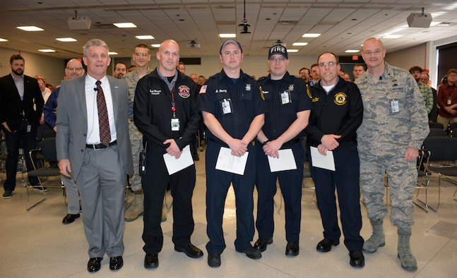 Personnel from the AFRL Materials and Manufacturing Directorate look on as Mr. Thomas Lockhart (left), Director, honors Inspector Garth Musgrove, Engine 32 representative Abram Berry, Engine 31 representative Zacherias Thorpe, and District Chief Kevin Narad of the Wright-Patterson Air Force Base Fire Department on April 12 for their quick response to a flooding event at the directorate.  Brigadier General Allan Day, Commander, Defense Logistics Agency Aviation, was also present at the event to offer his thanks.  (U.S. Air Force Photo/David Dixon)