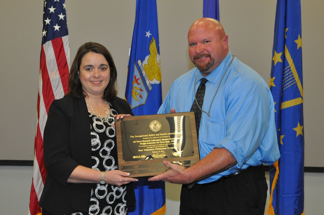Kenneth Montgomery, Occupational Safety and Health Administration Area Director of the Cincinnati Area Office, presents an OSHA VPP Star status plaque to Ruth Moser, director of AFRL's Sensors Directorate. The Sensors Directorate is one of only 56 certified VPP Star sites in the Department of Defense and one of less than 2,300 OSHA certified VPP Star sites in the country. (U.S. Air Force photo/Bryan Ripple)