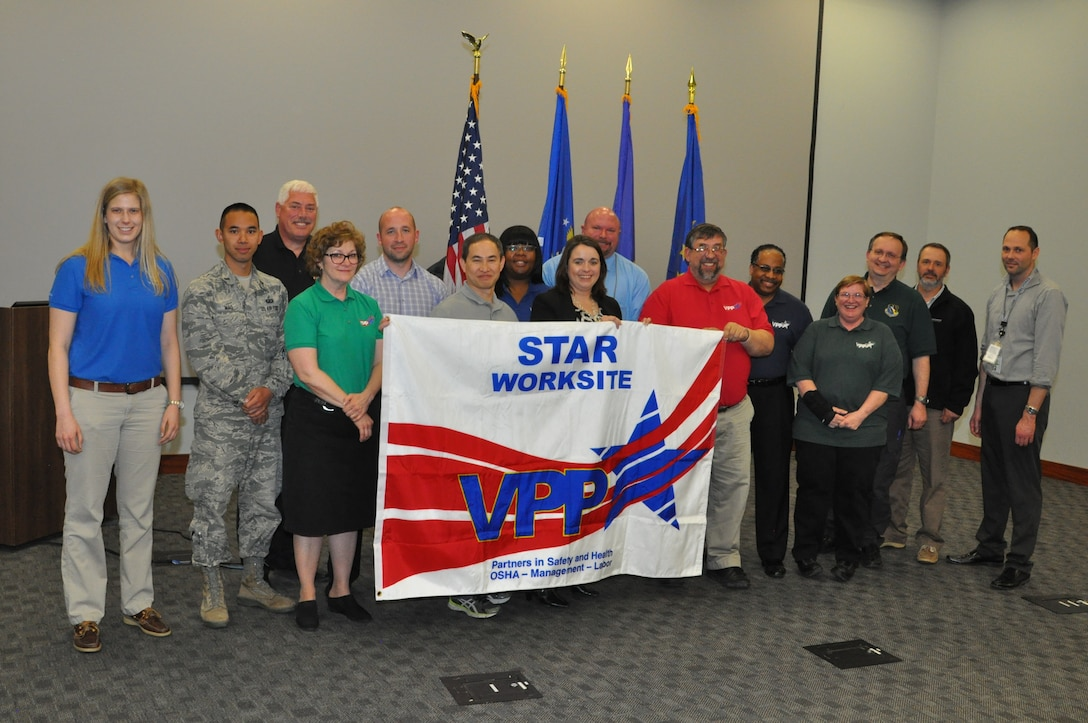 Employees and management officials from the Air Force Research Laboratory Sensors Directorate, along with Occupational Safety and Health Administration officials, display OSHA's Voluntary Protection Program Star Site banner during an April 14 ceremony recognizing the Sensors Directorate as just the 56th certified VPP Star site in the DOD. (U.S. Air Force photo/Bryan Ripple)