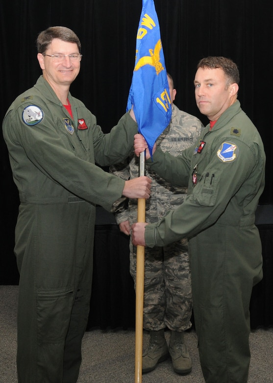 Lt. Col. Jared Kennish receives the 131st Operations Group guidon from Col. Mike Francis, 131st Bomb Wing commander, during the assumption of command ceremony at Whiteman Air Force Base, Missouri, April 17.   (U.S. Air National Guard photo by Sr. Airman Nathan Dampf)