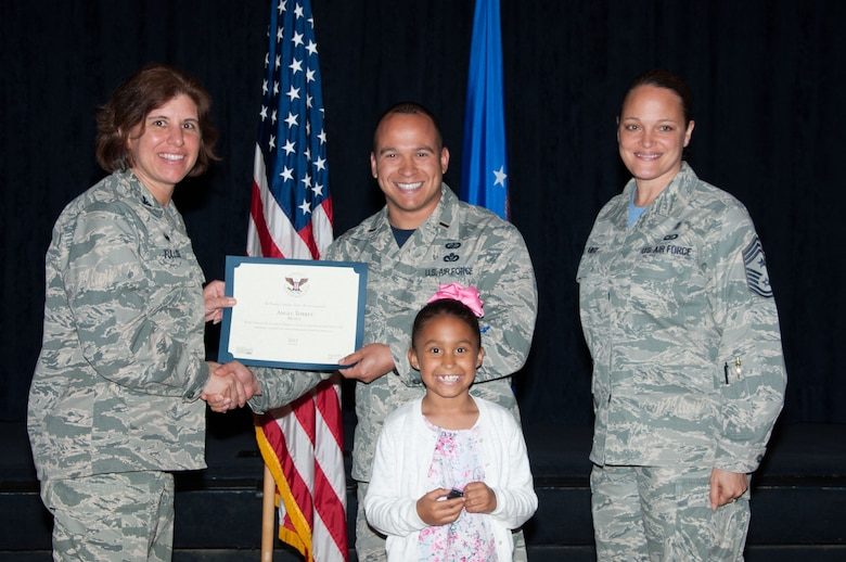 Isabella Torres poses with her father, 2nd Lt. Angel Torres, Air Force Life Cycle Management Information Technology Business Analytic Office program manager, as he receives his Presidential Volunteer Service Award, during the Volunteer Recognition Awards ceremony, April 15, 2016, Maxwell Air Force Base, Ala. Along with her father, Isabella also earned the same award, making her Maxwell's youngest volunteer to be recognized. (U.S. Air Force photo by Airman 1st Class Alexa Culbert)
