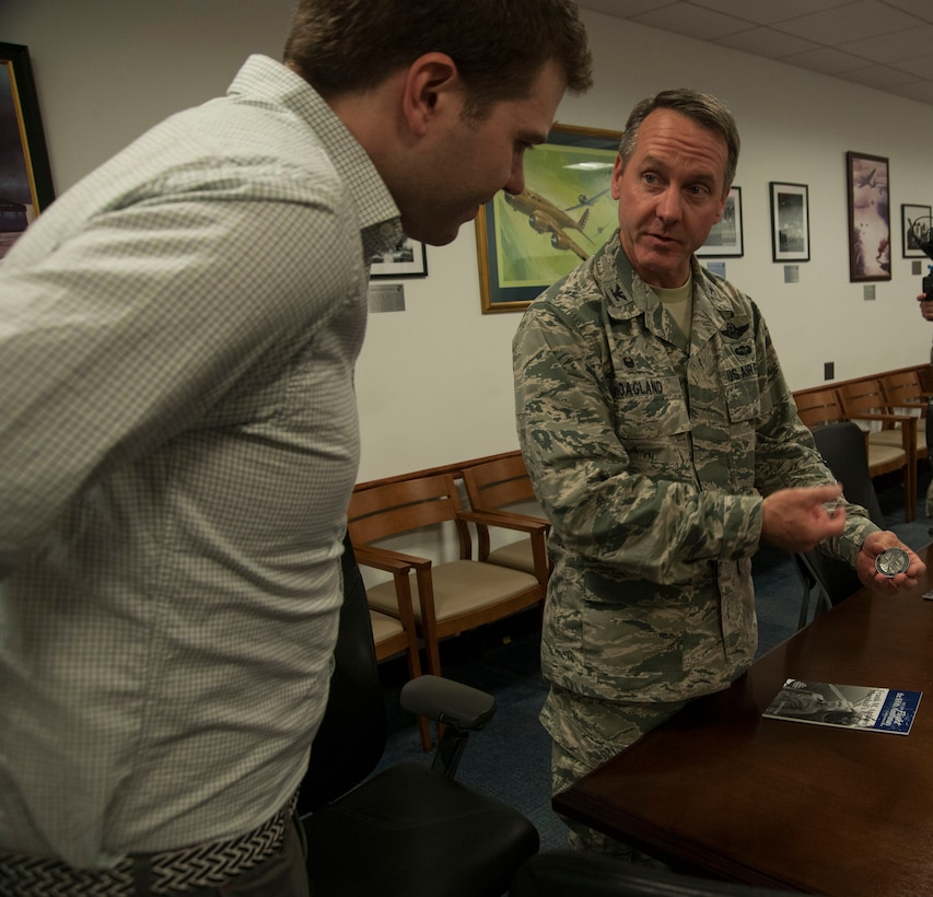 Col. Bradley Hoagland, 11th Wing and Joint Base Andrews commander, explains the meaning of the commander's coin to James David Andrews V, on JBA, Md., April 14, 2016. Andrews, the great-great nephew of deceased Lt. Gen. Frank M. Andrews and whom the base is named after, was presented the coin. (U.S. Air Force photo by Airman Gabrielle Spalding/Released)