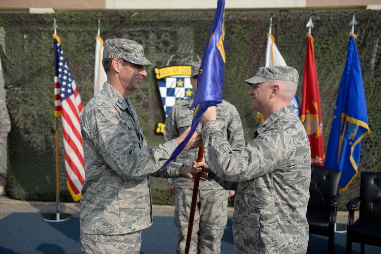 """U.S. Air Force Col. David Mineau, 18th Operations Group commander, presents the new 623rd Aircraft Control Squadron guidon to Lt. Col. Daniel Biehl, 623 ACS commander, during a re-designation ceremony April 15, 2016, at Kadena Air Base, Japan. The 623rd Air Control Flight """"Lightsword"""" transitioned back into a squadron for the first time in more than 20 years at 4:23 p.m. (U.S. Air Force photo by Senior Airman Stephen G. Eigel)"""