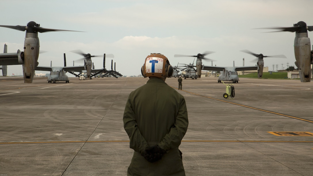 A Marine waits to guide MV-22 Ospreys with Marine Medium Tiltrotor Squadron 265, 31st Marine Expeditionary Unit, during their takeoff April 17 on Marine Corps Air Station Futenma. United States Forces, Japan is providing operational airlift support in coordination with the Government of Japan's efforts to provide relief following the devastating earthquake near Kumamoto.