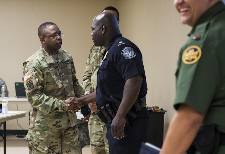 Maj. Gen. Phillip Churn, commanding general of the 200th Military Police Command, shakes hands with Supervisory Customs & Border Protection (CBP) Officer, Marecus Matthews, after he and another CBP officer provided a briefing on the career opportunities available to U.S. Army Reserve military police Soldiers at the MP command's headquarters at Fort Meade, Maryland, April 16. (U.S. Army photo by Master Sgt. Michel Sauret)