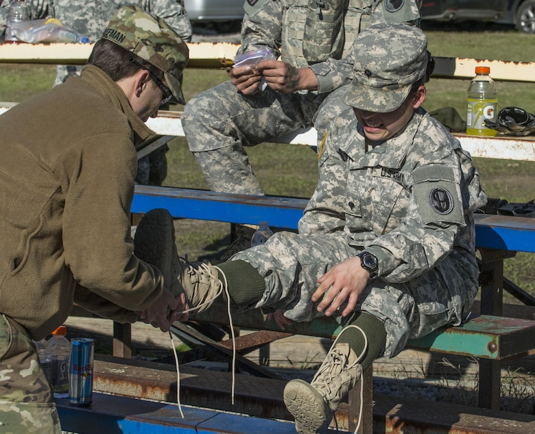 Spc. Kayla Bundy, 1st Bn., 414th Inf. Reg., 95th Training Division (IET), gets a bit of help removing her boots after completing a 10-mile forced march during the 2016 108th Training Command (IET) Best Warrior competition held at Fort Jackson, S.C., March 21. This year's Best Warrior competition determined the top NCO and junior enlisted Soldier who will represent the 108th Training Command (IET) at the Army Reserve Drill Sgt. of the Year competition later this year at Fort Bragg, N.C. Bundy was selected to represent the 108th in the junior enlisted competition. (U.S. Army photo by Sgt. 1st Class Brian Hamilton/released)