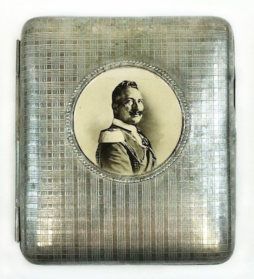 The front exterior of this metal cigarette case displays a photo of Kaiser Wilhelm II, who was the last King of Prussia. He reigned from 1888 to 1918. His great-uncle was Frederick Wilhelm IV, who in 1842 designed the pickelhaube, which became the helmet worn by the Prussian army. Capt. Edward V. Rickenbacker, America's highest scoring ace of WWI, brought this Prussian cigarette case home as a wartime souvenir. It is unknown how he attained it.