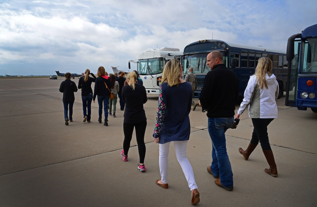 Military spouses head out to busses on the flightline during Spouse Flight Day April 15, 2016, at Cannon Air Force Base, N.M. Dozens of dependents were provided a rare opportunity to fly aboard 27th Special Operations Wing aircraft and gain operational insight to Cannon's role in the Air Force Special Operations Command mission. (U.S. Air Force photo/Staff Sgt. Alexx Pons)