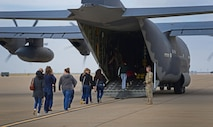 Military spouses prepare to board an MC-130J Commando II during Spouse Flight Day April 15, 2016, at Cannon Air Force Base, N.M. Aircrew members provided overviews of the unique missions they perform in direct support of Air Force Special Operations Command. (U.S. Air Force photo/Staff Sgt. Alexx Pons)