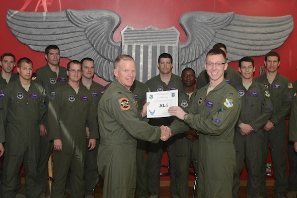 """1st Lt. Nicholas Atkins, 434th Flying Training Squadron X-Flight unit standardization and evaluation manager and T-6 Texan II instructor pilot, accepts the """"XLer of the Week"""" award from Col. Darrell Judy, 47th Flying Training Wing vice commander, here, April 11, 2016. The XLer is a weekly award chosen by wing leadership and is presented to those who consistently make outstanding contributions to their unit and Laughlin. (U.S. Air Force photo by Airman 1st Class Brandon May)"""